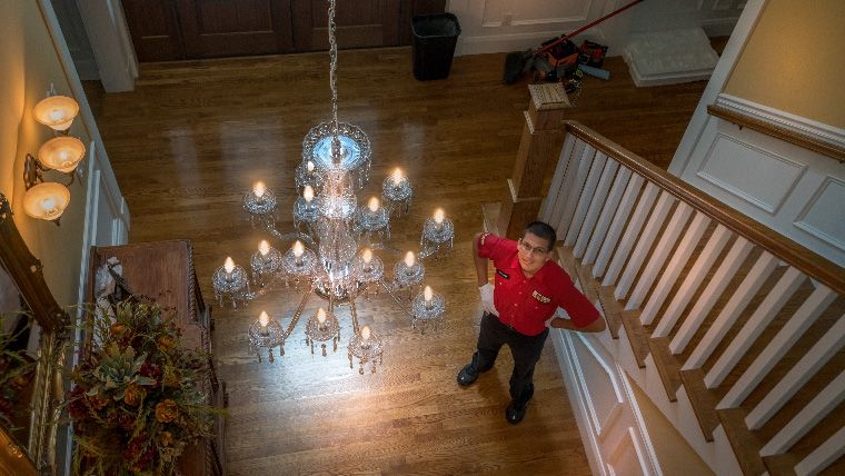 Electrician looking up at a crystal chandelier