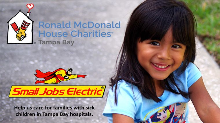 Little girl smiling at the camera with Ronald McDonald House Charity logo