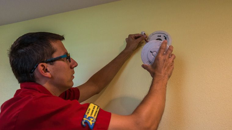 Electrician working on a smoke alarm